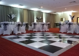 blackand white dancefloor white chaircovers black sash and feathers at portsmouth marriott